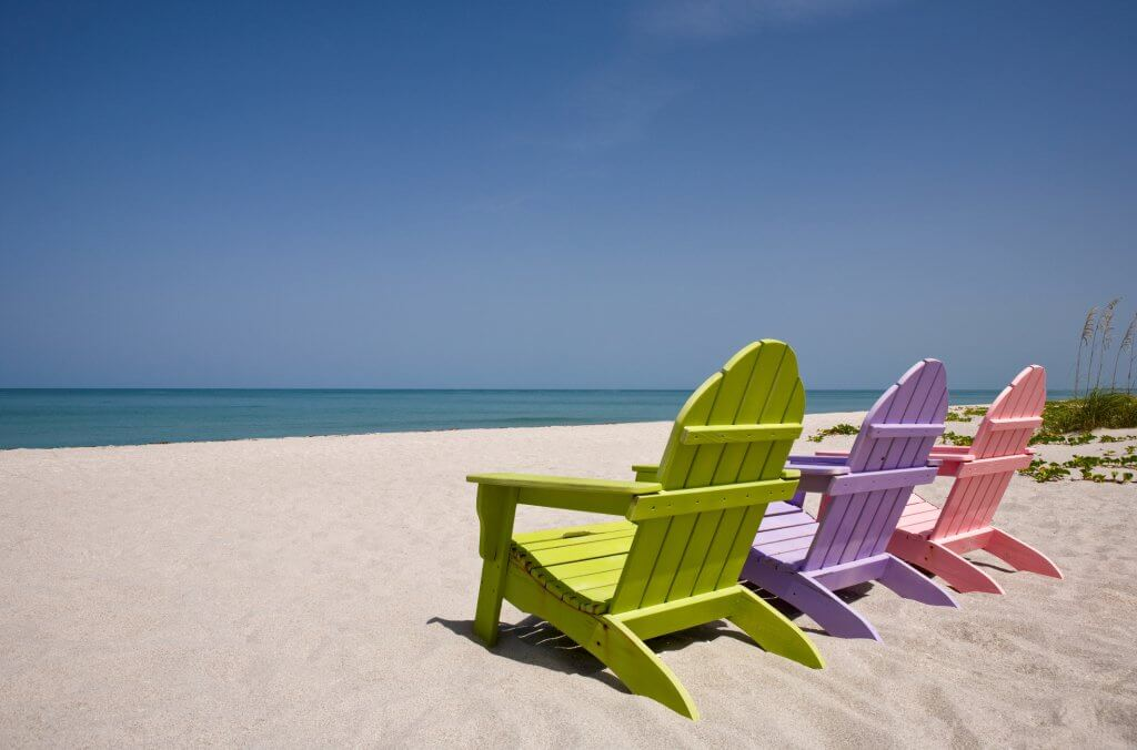 Three pastel colored beach chairs on sand overlooking a turquoise sea.